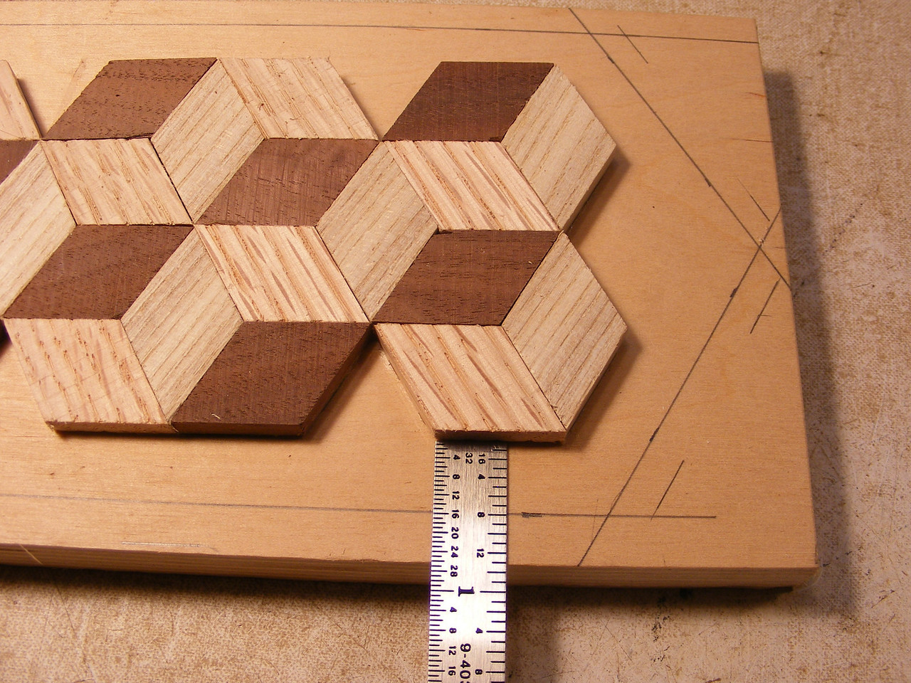 "11 - Making a Tumbling Block Cribbage Board <br /> After the glue is trimmed off I then mark out from the diamonds ½"", all around. At the ends I will lay a diamond in the point and measure from it, then draw connecting lines all the way around."