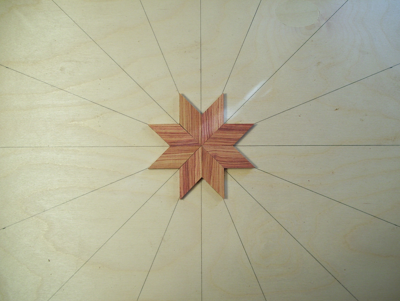 """Making a Lazy Susan #2<br /> Take a piece of ½"""" Baltic Birch Plywood and drew 8 lines clear across it, intersecting in the middle, equally spaced. They will be used to help guide the inner and outer points of the star, to try and keep them on the line. In the first and second pictures I have the lines drawn and the first 8 diamonds glued on forming the center of the star."""