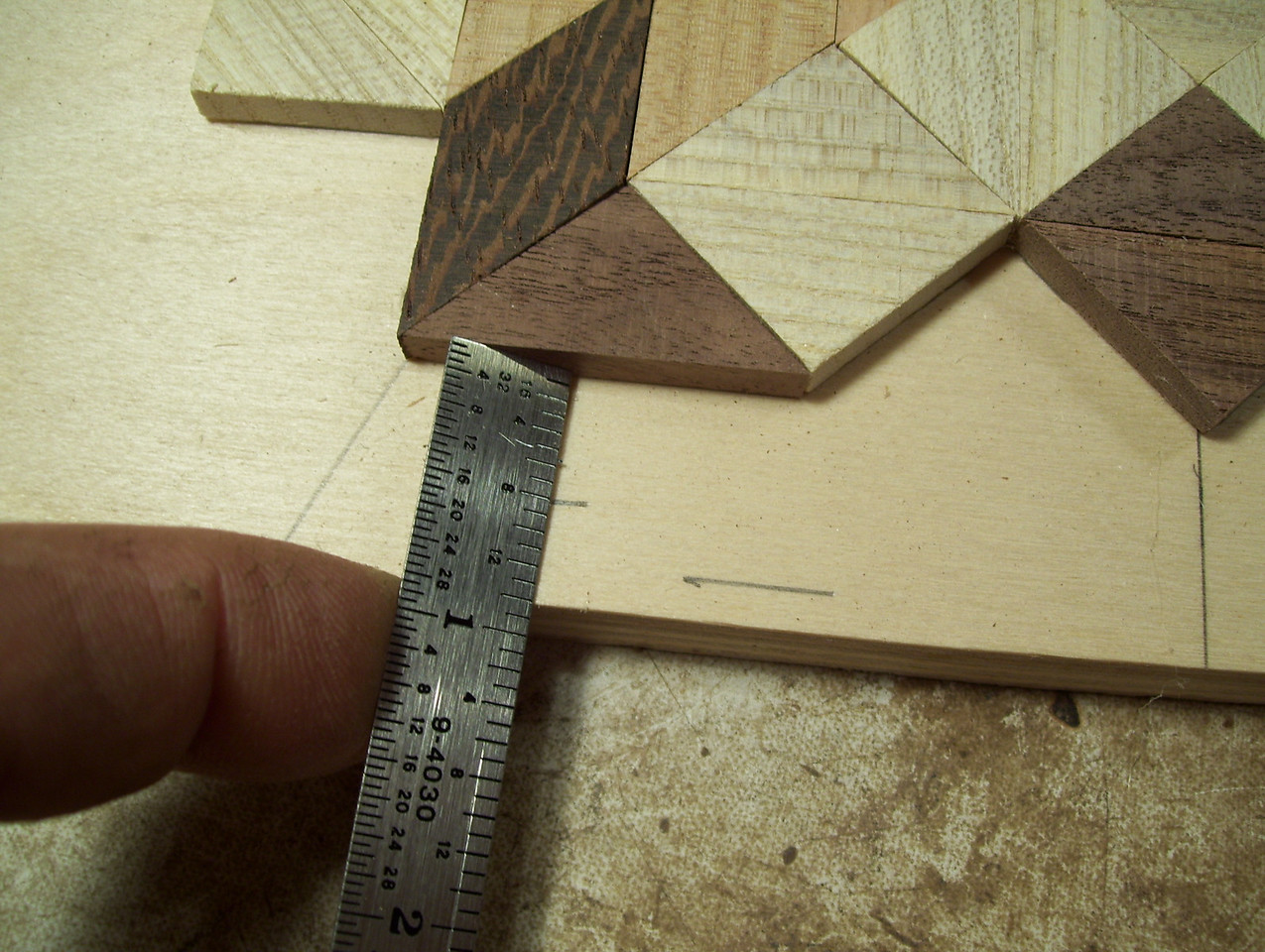 "Making a Lazy Susan #24<br />  I then lay a triangle in the space and measure out ½"" all the way around the star. The short line you see here is the cutoff line. The longer line is the line the pieces will come out to when the top is all laid out."