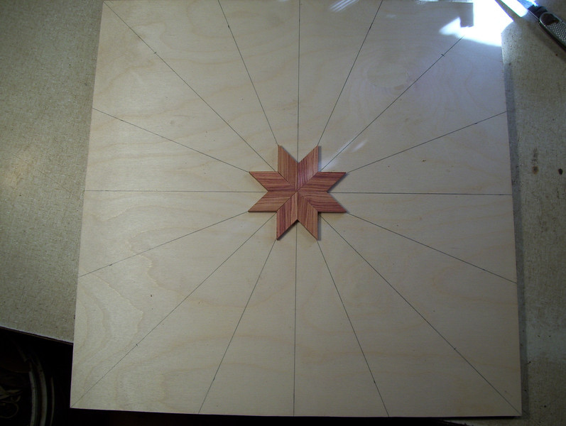 "Making a Lazy Susan #1<br /> Take a piece of ½"" Baltic Birch Plywood and drew 8 lines clear across it, intersecting in the middle, equally spaced. They will be used to help guide the inner and outer points of the star, to try and keep them on the line. In the first and second pictures I have the lines drawn and the first 8 diamonds glued on forming the center of the star."