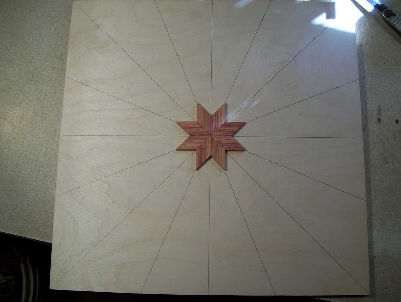 """Making a Lazy Susan #1<br /> Take a piece of ½"""" Baltic Birch Plywood and drew 8 lines clear across it, intersecting in the middle, equally spaced. They will be used to help guide the inner and outer points of the star, to try and keep them on the line. In the first and second pictures I have the lines drawn and the first 8 diamonds glued on forming the center of the star."""