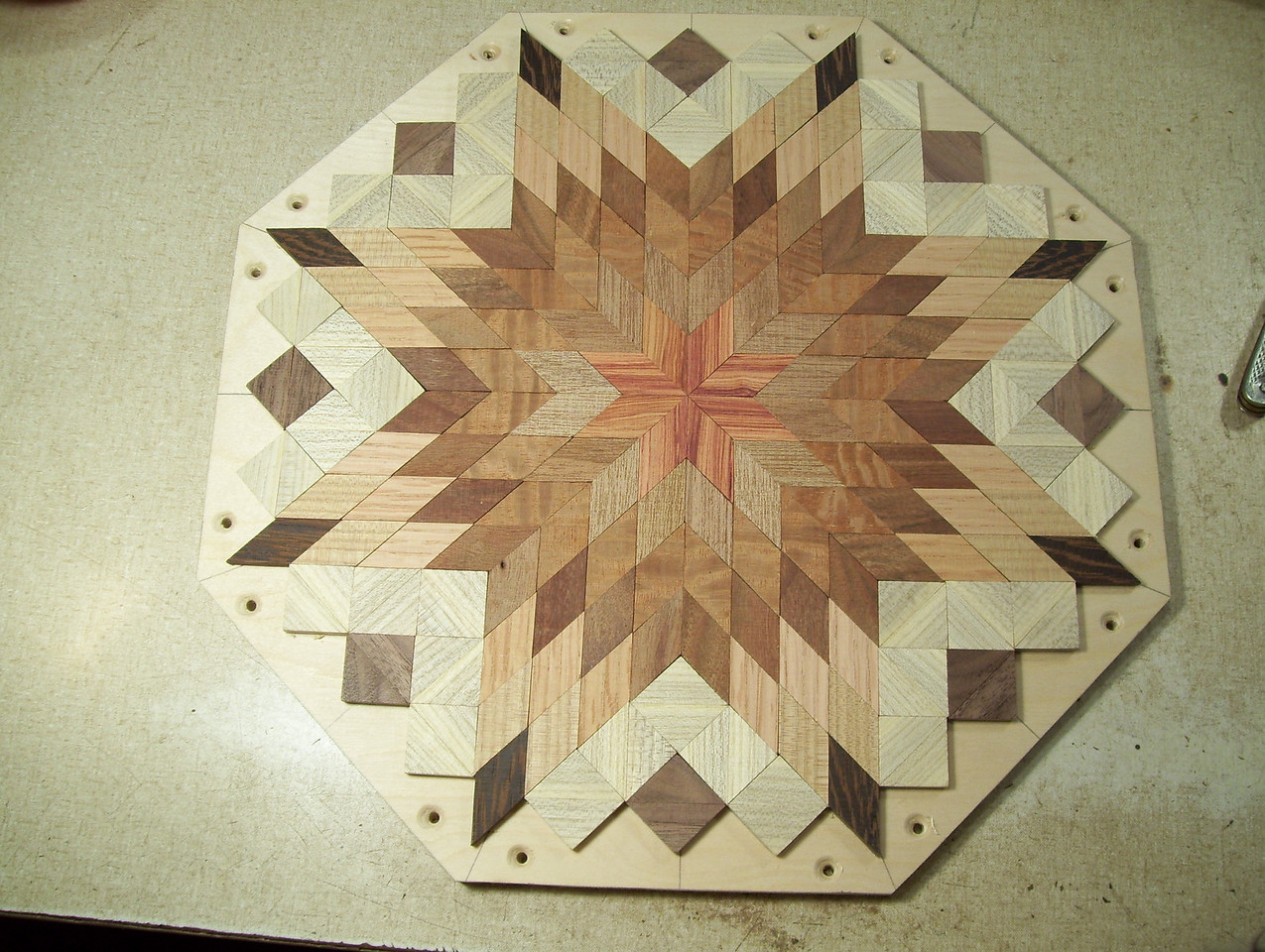"""Making a Lazy Susan #28<br /> After I cut it to shape I measure in 3/8"""" at each end of each side, drill it and counter sink the drill hole all the way around the edge of the lazy susan."""