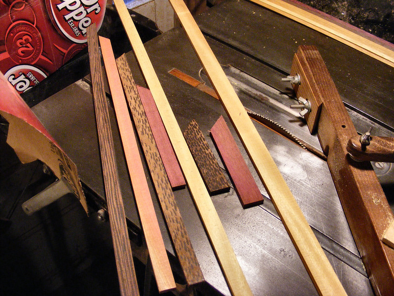 """#1 Making a Tiny Sq Box<br /> I recently started using some Brazilian Satinwood that has perfect satinwood markings on the surface of the wood, so I thought I had to make several tiny boxes with some of it. All of my boxes are put together basically the same. The larger boxes I do lay out the pieces on the top out to the last row that goes over the edge. On the larger boxes I then measure out and cut it to shape then, they are not always the same. <br /> <br /> On this box I wanted the same coloring as on my other Sri Lanka Satinwood box, the only difference is that I'll start this one off with Wenge in the center. I would then use Pink Ivory, Black Palm (cut on an angle to give the dots of the end grain an elongated look to make it more interesting), Purpleheart and then Satinwood. I will use the Aunt Sukeys Choice quilt pattern on the top. It will have a mixture of half size pieces on the top and full size pieces on the sides. This first picture shows the different woods in the different size of strips that I will be using, along with the jig I use to cut the full size triangle. I have 3 other jigs I will use to cut the other 3 type of pieces on the box. (You can find more on the jigs and cutting my pieces on my """"How I Make a Lazy Susan"""" set (or Blog))"""