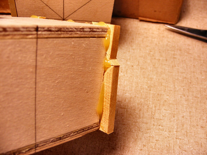 #10 Making a Tiny Sq Box <br /> In gluing the pieces to the sides or ends of the box, they will hang over front and back. When I glue the pieces onto the front and back, they will go over the edges of the pieces on the ends and the pieces on the top will overhang on all sides.<br /> <br /> The glue you see here will need to be shaved off