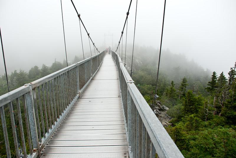 Swinging bridge on a foggy day