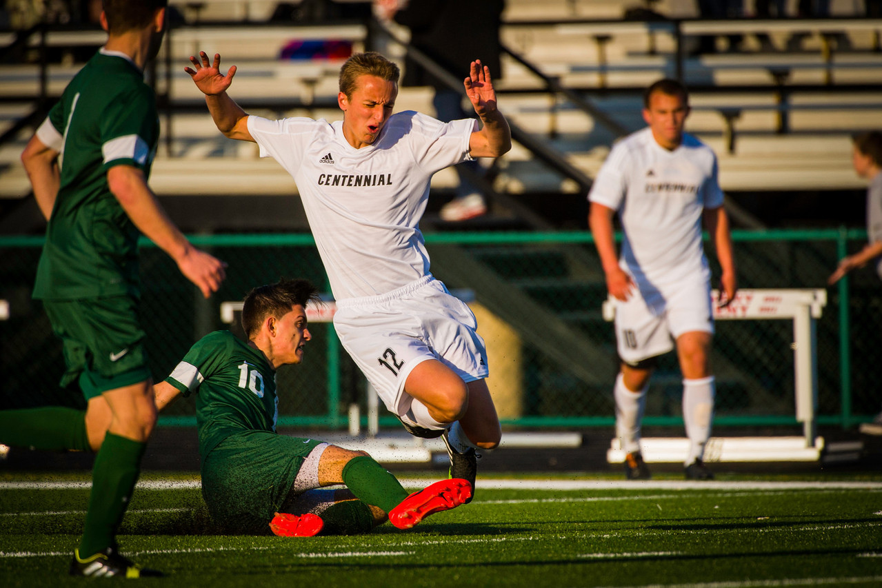 Nermin Kremic (12), Junior, Midfielder/Forward, finds himself airborne after a Hoover player connects during a slide tackle when Ankeny Centennial High School Boys Varsity Soccer Team played Hoover High School