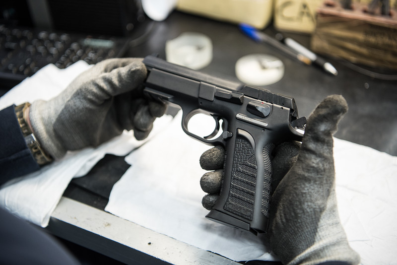 "February, 2018 – Val Trompia, Italy. An employee checks a Force 99 handgun on the production line. Tanfoglio polymer framed Force pistols are popular defensive and sporting firearms across the Europe. They also are imported into USA by EAA Corp. under the name ""Witness Polymer"" (Force) and ""Witness Polymer P"" (Force 99). It is widely used by special units (SWAT type) of foreign police forces"