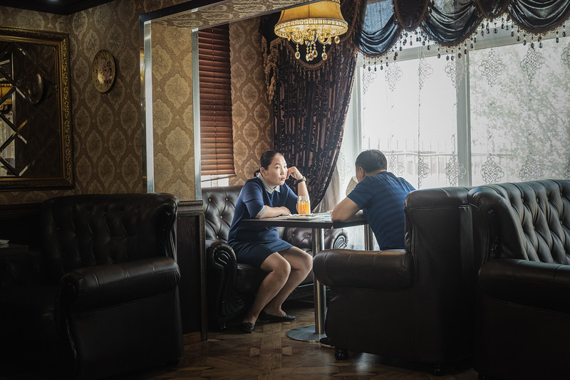 """Mongolia, Cogtcėcij, 2019. A Chinese businessman with his wife at the """"Broadway"""" restaurant, the only restaurant for foreigners in Cogtcėcij, near Tavan Tolgoi mine. Mongolian mining business is heavily dependent on demand for coal and copper from China, its southern neighbour and the buyer of more than 90 percent of its exports."""