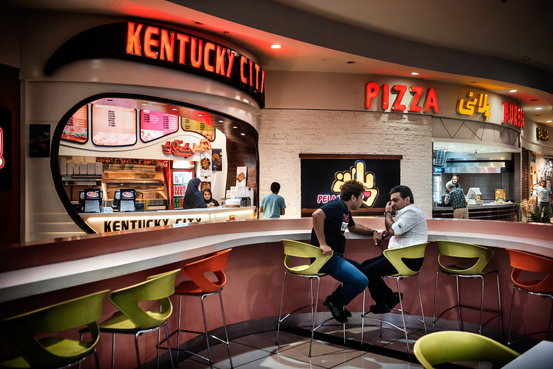 """August 16, 2017 – Isfahan, Iran. Customers at the """"Kentucky City"""" one of the fast food restaurants inside the Isfahan City Center Mall. In the past decade, fast food restaurants have spread like wildfire throughout Tehran and much of the country. Although the US and Iran have no diplomatic relations, restaurant owners have attempted to emulate American fast food franchise. Since the early 2000s, bootleg American fast food franchises have made their way throughout the country and have captured the hearts and taste buds of Iranians alike. ''Kentucky City'' has been one of the first franchises to open in Iran. © Simone Tramonte"""