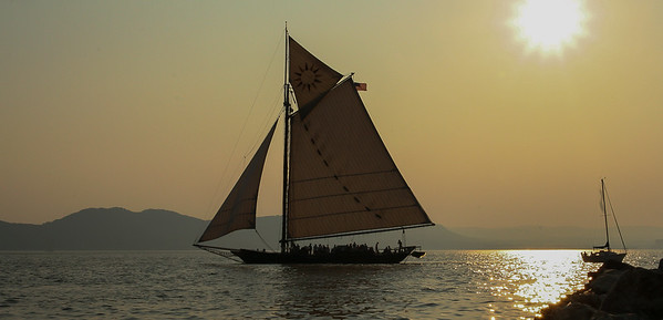 The Hudson River Sloop Clearwater passing Croton Park at sunset during the Clearwater Festival.