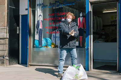 A man puts his gloves on before entering the dry cleaners.