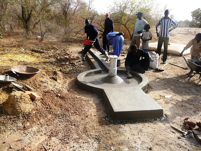 The cement is poured and shaped. The handpump will be fastened atop the post. Any overflow will run into the trough in the back. If the animals of Thiou are like the animals of Wunlang, they'll quickly find the trough as a new source of water for themselves.