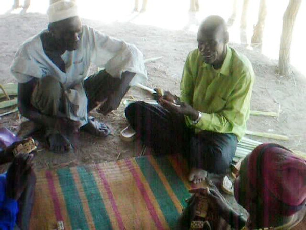 Even as the classrooms were finished, they became social centers. Here men are playing dominoes.