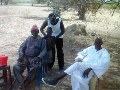 Bol met with the village elders, including his father (on the right).