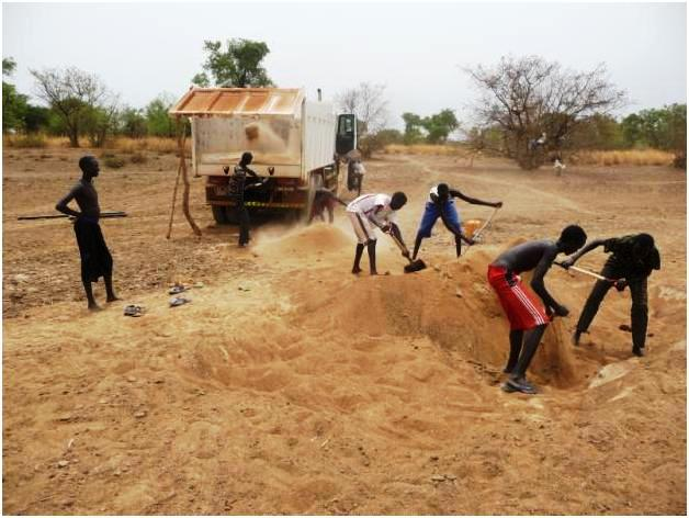 Sourcing sand for the construction involves a lot of labor, but these villagers dig in to play their part in making Thiou Freedom School a reality.