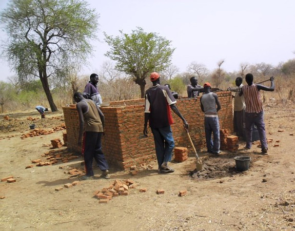 The kitchen under construction. It looks small, but cooking is usually done indoors only when it's raining. It will also be a place to keep food supplies safe and dry. <br /> <br /> Here also is another example of how Village Help for South Sudan uses local labor.