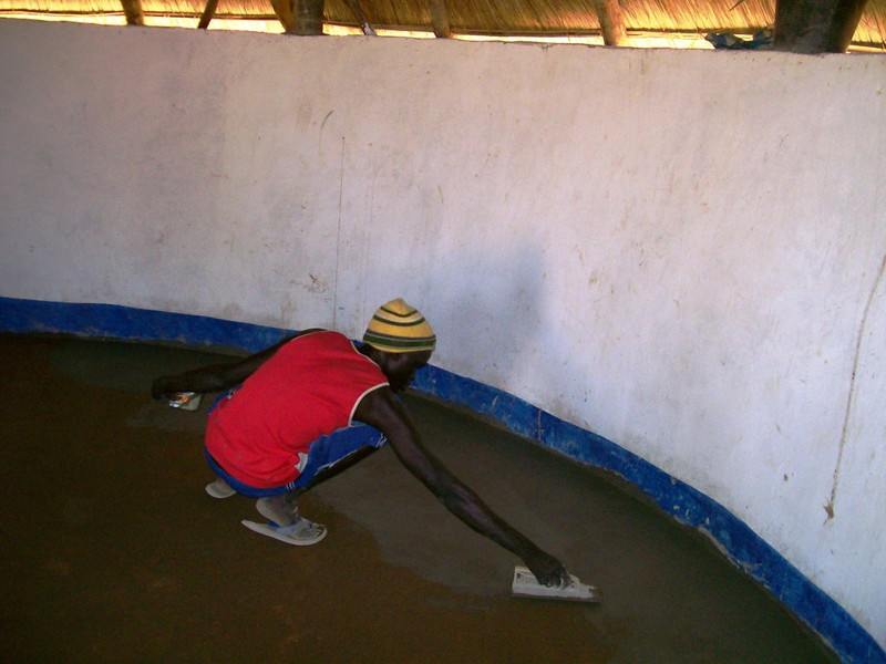 Local mason from Wunlang finishes the floor in one of the guest houses.
