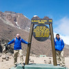 """Jeff and Max Crider celebrate after reaching the """"Lava Tower"""" monument at 15,000 feet. Mount Kilimanjaro is behind them."""