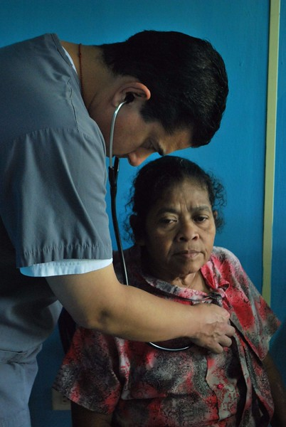 Dr. Ed Mena, a hepatologist at Huntington Memorial Hospital in Pasadena, Calif., examines a patient during the IMAHelps medical mission to Matagalpa, Nicaragua.