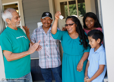 The Hernandez family cuts down the celebratory ribbon and receives the keys to their new home during the Habitat for Humanity of Butte County Home Dedication Ceremony as Habitat board member Richard Macias, left, looks on Saturday July 15, 2017 in Chico, California.  (Emily Bertolino -- Enterprise-Record)