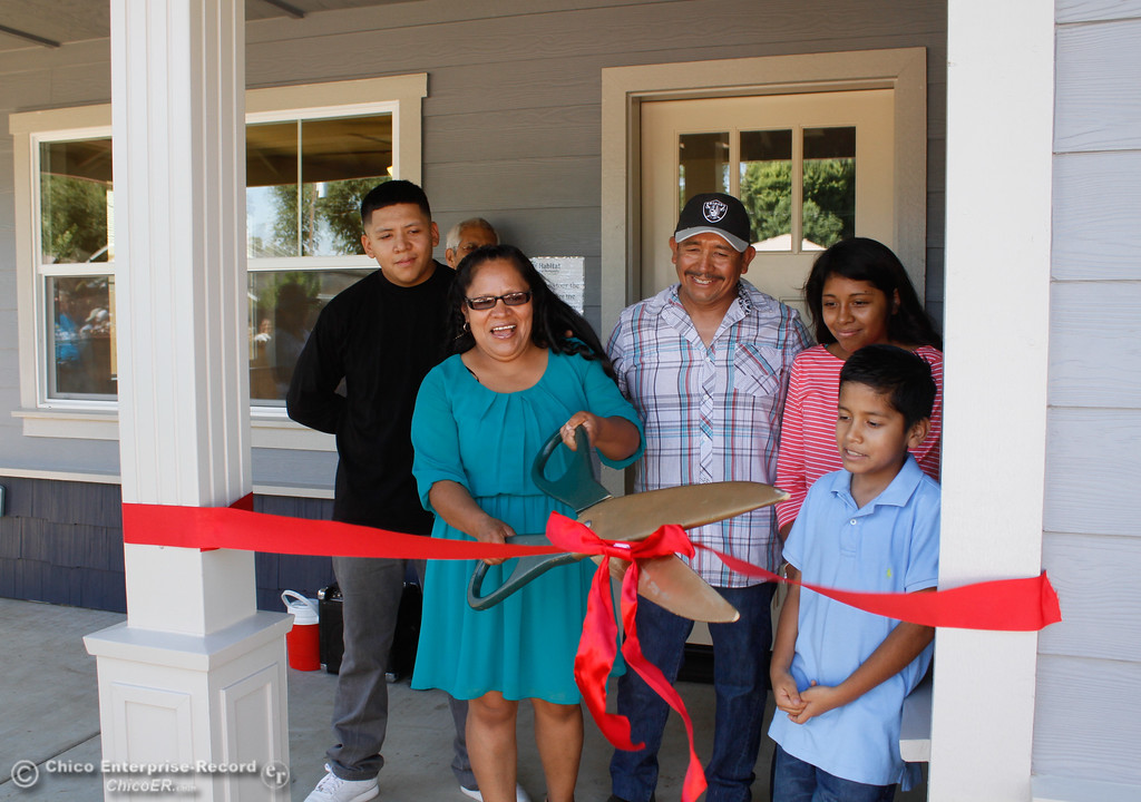 . The Hernandez family cuts down the celebratory ribbon and receives the keys to their new home during the Habitat for Humanity of Butte County Home Dedication Ceremony Saturday July 15, 2017 in Chico, California.  (Emily Bertolino -- Enterprise-Record)