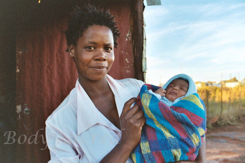"""Mother<br /> South Africa ©2004<br /> This mother came out of her small tin home to introduce us to her new baby.  Rose was just a week old.  The eyes of the mother are magnetic.  They draw us in and say, """"I see you…I am you…we are one"""""""
