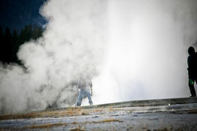 2 people walking through a small geyser eruption