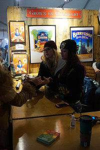 Tiffanie Verhine, left, and Alissa Bernhardt help a customer try out the products at the Graham's Brand booth  during the Humboldt County Cup in Redway on Saturday, Jan. 21. (Kellie Ann Benz - The Redwood Times)