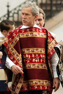 U.S. President Bush, wearing a traditional handmade Chilean poncho pauses during the APEC leader's official photograph at the Naranjos Courtyard at La Moneda Sunday, Nov. 21, 2004,in Santiago, Chile.  The woolen ponchos were hand-woven by a group of eight women in the town of Donihue, about 200 kilometers (125 miles) south of Santiago, the capital. Each poncho takes up to four months to make. (AP Photo/Pablo Martinez Monsivais)