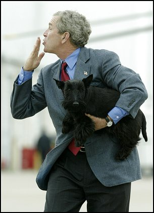 U.S. President George W. Bush blows a kiss to well-wishers as he carries his dog Barney to Air Force One at the TSTC airport in Waco, Texas, April 12, 2004. Bush is returning to Washington after spending the Easter weekend at his ranch in Crawford, where he also held a press conference Monday with Egyptian President Hosni Mubarak.   REUTERS/Jason Reed