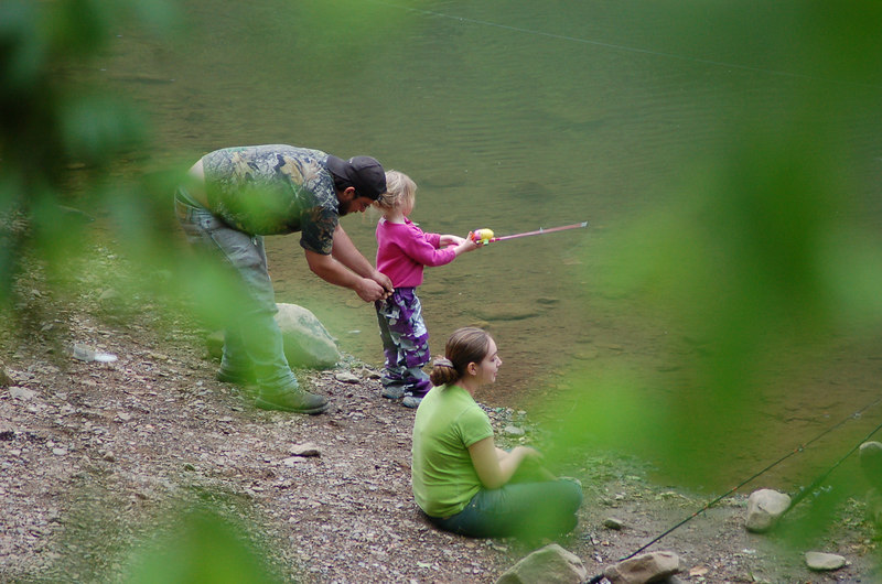 This young lady was the 'ultimate fisherman' on the New River in West Virginia.   She was so busy casting and reeling in, that she didn't notice that her pants had fallen down!   But dad came to the rescue and fixed the situation, though I don't think she noticed... she never missed a cast the whole time.<br />    (This photo was taken in the open from a highway next to the river.)