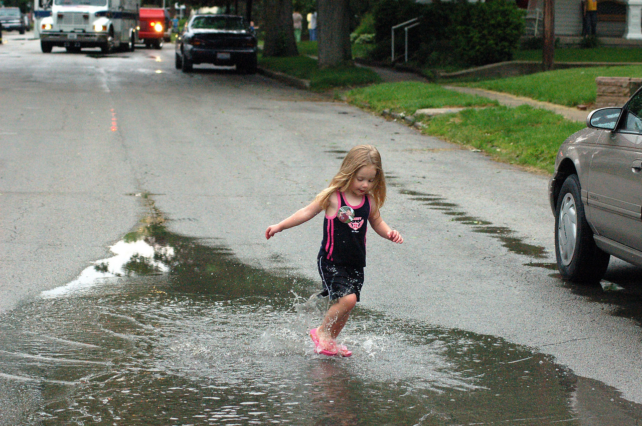 This little girl found that  jumping in a water puddle on a closed street was more interesting than the fire and EMS vehicles parked behind her.   Lightning from a severe thunderstorm struck three houses in her neighborhood.