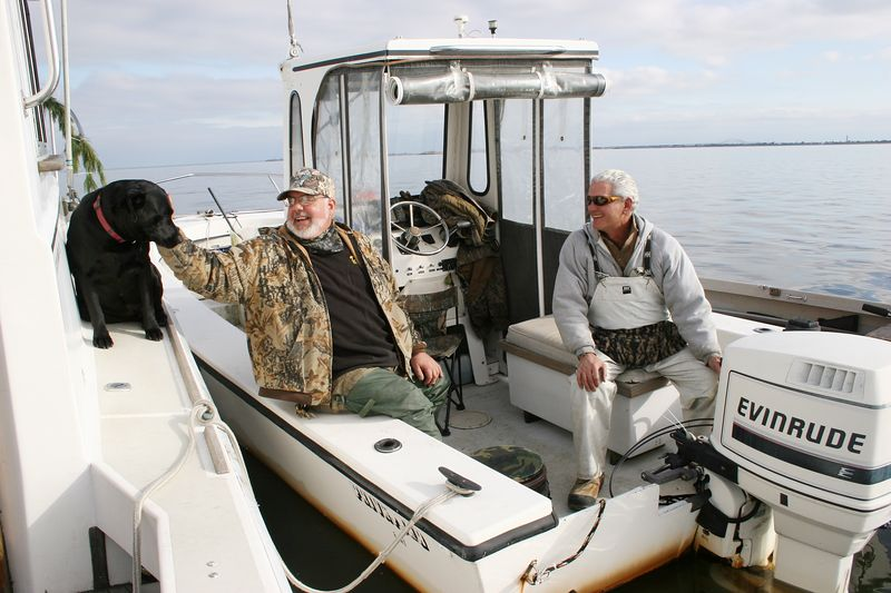 <b>1/9/2005</b> John and I were playing with Diesel while we were hanging out on the mother boats.  Jim Conte was in the hunting scooter and as you can see from the photos the wind totally died and Jim didn't get any shots during his half-hour stay.  Late in the day the wind came up a little and we got some cloud cover and did take down a few birds.