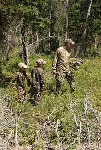 Dad showing young boys about archery hunting.  Photo taken 8-19-08, courtesy of Utah Division of Wildlife Resources