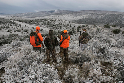 Four hunters searching for game in hills with light snow cover.