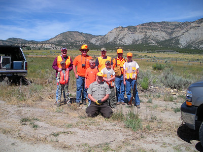 Conservation officer Ben Riley kneels in front of youth chukar hunters near Price, Utah.
