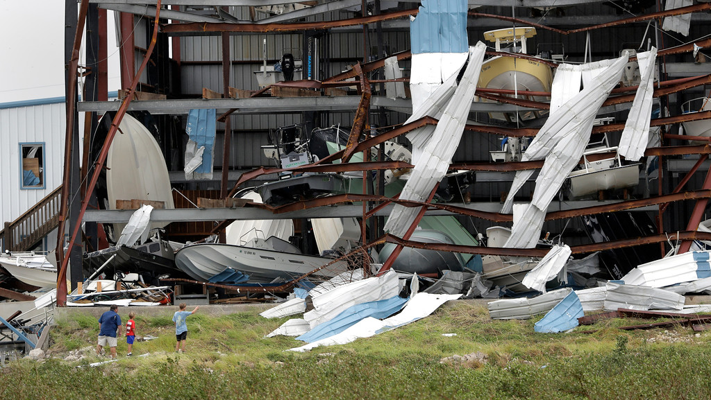 . A group stops to check out damage to a boat storage facility caused by the effects of Hurricane Harvey, Sunday, Aug. 27, 2017, in Rockport, Texas. (AP Photo/Eric Gay)