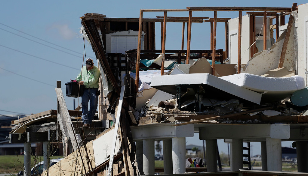 . Shane Johnson removes items from a family home destroyed in the wake of Harvey, Tuesday, Aug. 29, 2017, in Rockport, Texas. AP Photo/Eric Gay