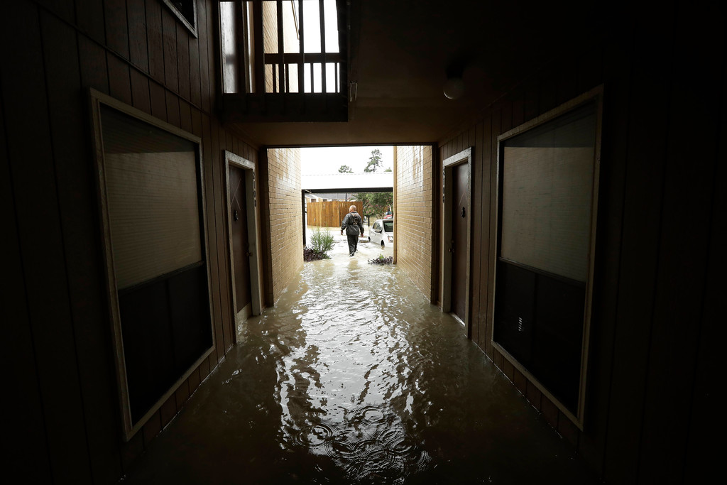 . Steven Hathaway searches for people to help in an apartment complex as floodwaters from Tropical Storm Harvey rise Tuesday, Aug. 29, 2017, in Kingwood, Texas. AP Photo/Gregory Bull