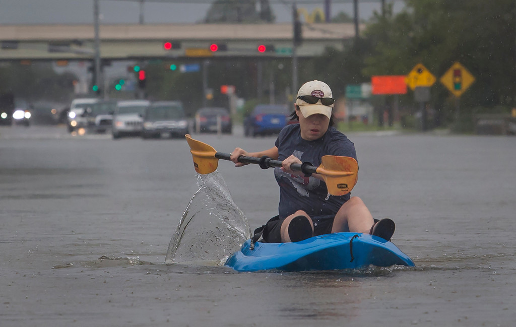 . A woman kayaks down a flooded section of FM 518 near the intersection with Interstate 45 in League City, Texas, on Sunday, Aug. 27, 2017.  The remnants of Hurricane Harvey sent devastating floods pouring into Houston Sunday as rising water chased thousands of people to rooftops or higher ground. (Stuart Villanueva/The Galveston County Daily News via AP)