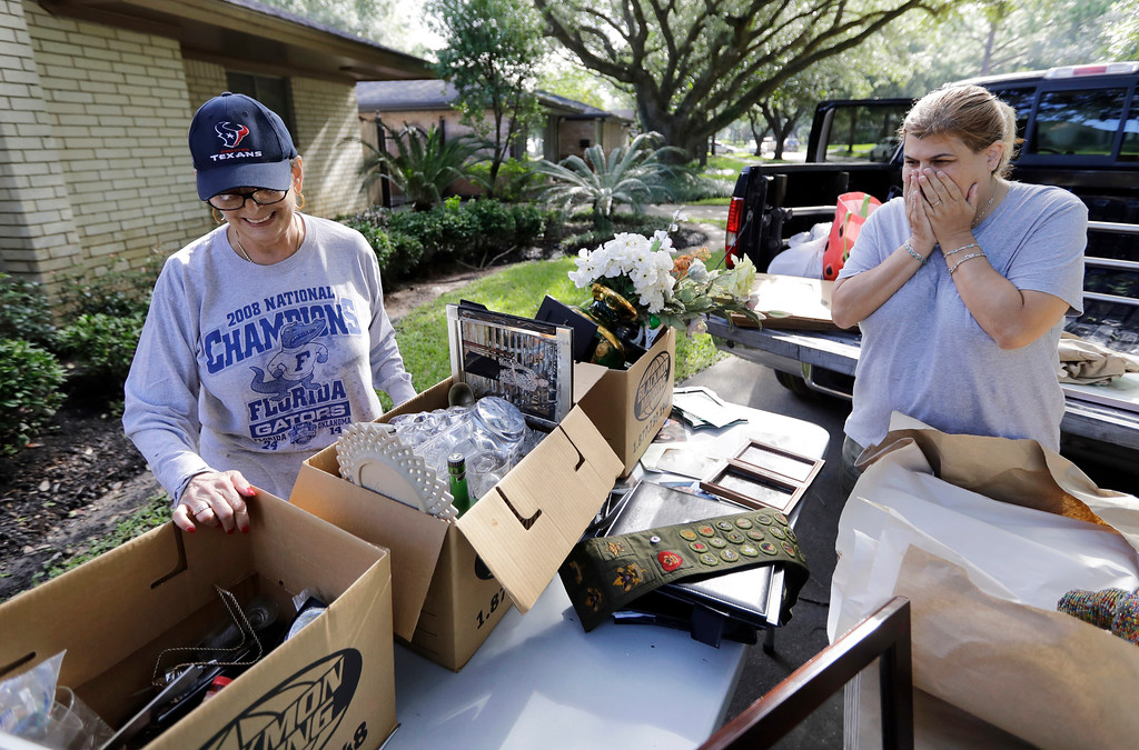 . Judy Mellon, left, is helped by her daughter, Beth Kendrick, as she sorts through items damaged by floodwaters from Tropical Storm Harvey Wednesday, Aug. 30, 2017, in Houston. Judy Mellon watched the storm from a neighbors home across the street which is built up as floodwaters spread through her home. (AP Photo/David J. Phillip)