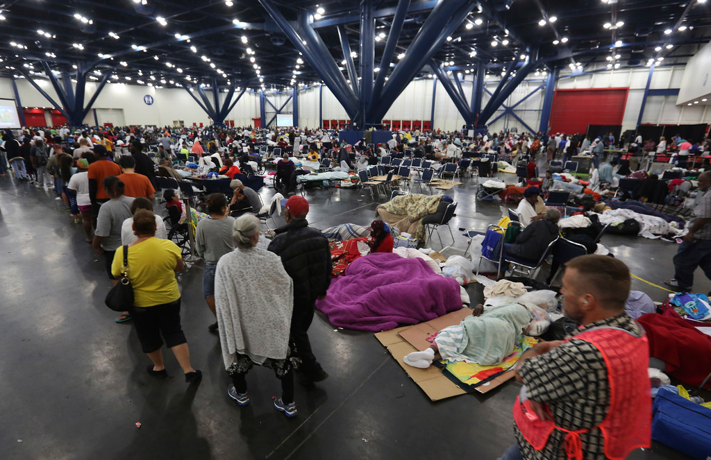 . People line up for food as others rest at the George R. Brown Convention Center that has been set up as a shelter for evacuees escaping the floodwaters from Tropical Storm Harvey in Houston, Texas, Tuesday, Aug. 29, 2017. AP Photo/LM Otero