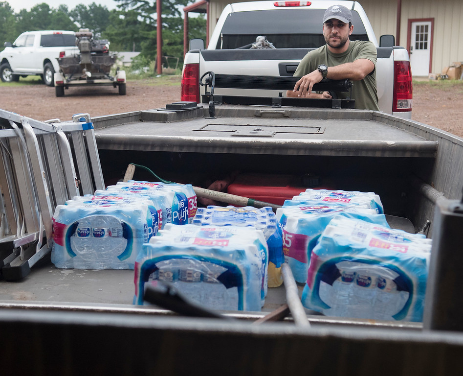 . Casey Korkmas of Tyler, Texas, helps pack supplies into a boat at WC Custom Boats in Noonday, Texas where several volunteers met to head to areas affected by Hurricane Harvey Monday morning Aug. 28, 2017. The group took six boats stocked with fuel and water headed to the Houston area to assist in Hurricane Harvey rescue efforts. (Sarah A. Miller/Tyler Morning Telegraph via AP)
