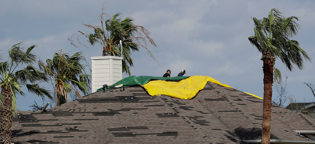 . Two men use tarps to cover a roof damaged by the effects Hurricane Harvey, Tuesday, Aug. 29, 2017, in Rockport, Texas. (AP Photo/Eric Gay)
