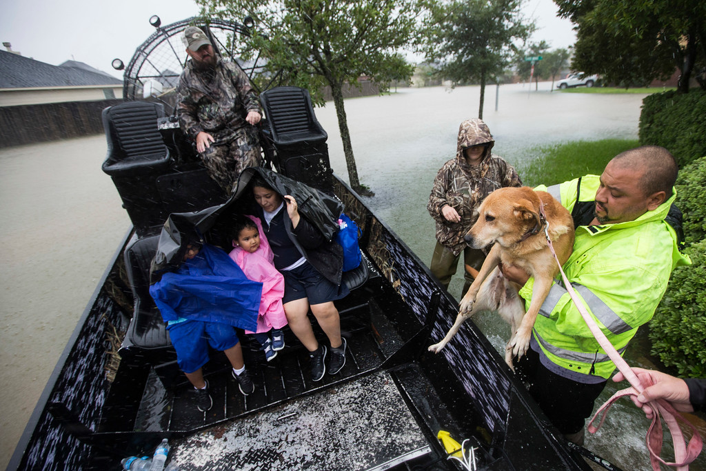 . Richard Velasco lifts his dog into an airboat as he and his family are evacuated from their home as water rises from heavy rains from Tropical Storm Harvey on Monday, Aug. 28, 2017, in Fort Bend County, Texas. (Brett Coomer/Houston Chronicle via AP)