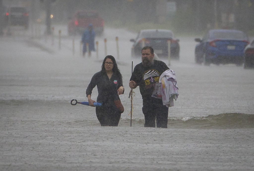 . People carry their belongings through flooded section of FM 518 near the intersection with Interstate 45 in League City, Texas, as rain from Tropical Storm Harvey continues to fall Sunday, Aug. 27, 2017. (Stuart Villanueva/The Galveston County Daily News via AP)