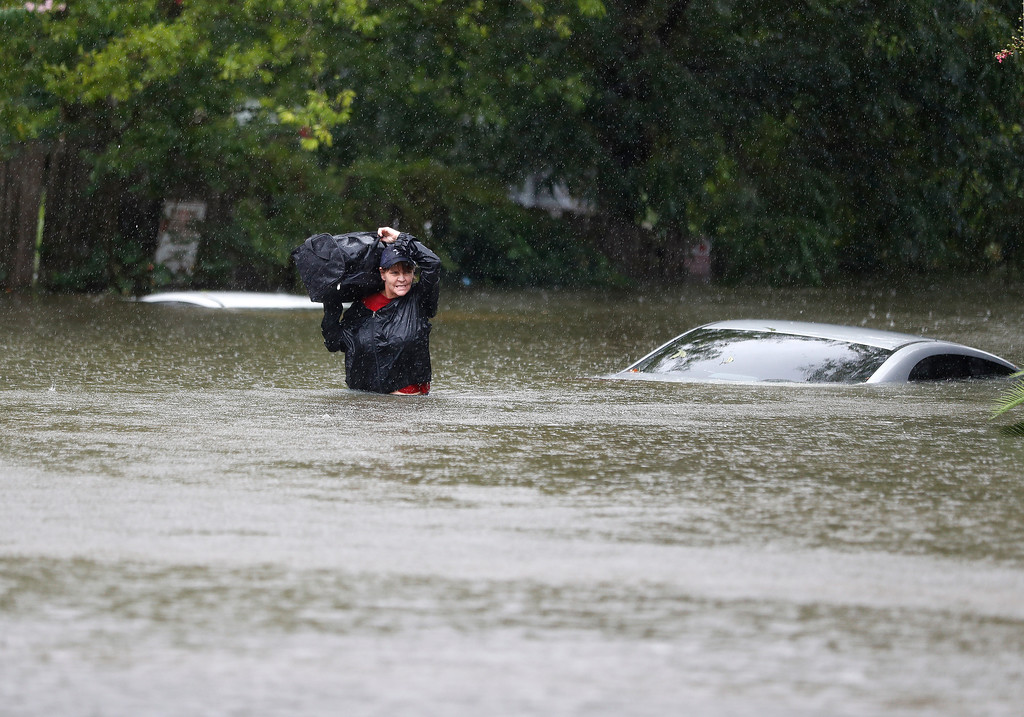 . Women carry belongings from an apartment under water on Houston Avenue near Woodland Park after heavy rain from Hurricane Harvey fell overnight, Sunday, Aug. 27, 2017, in Houston. The remnants of Hurricane Harvey sent devastating floods pouring into Houston Sunday as rising water chased thousands of people to rooftops or higher ground. (Karen Warren/Houston Chronicle via AP)