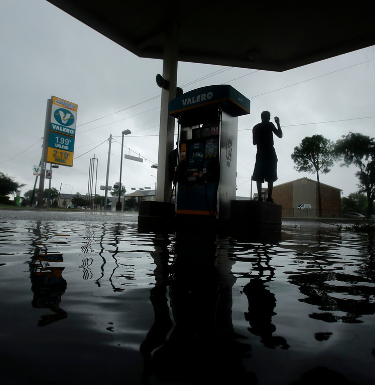 . A man watches heavy rain from the relative safety of a flooded gas station caused by Tropical Storm Harvey on Sunday, Aug. 27, 2017, in Houston.  The remnants of Hurricane Harvey sent devastating floods pouring into Houston Sunday as rising water chased thousands of people to rooftops or higher ground. (AP Photo/Charlie Riedel)