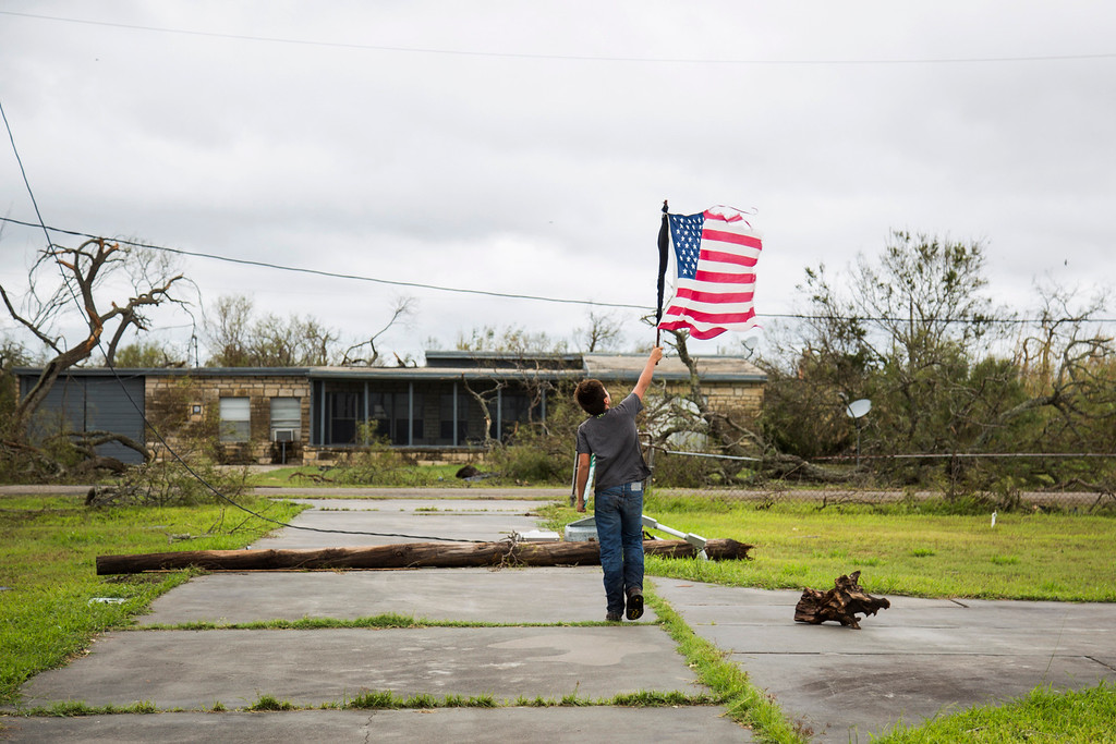 . CORRECTS DAY TO SUNDAY FROM SATURDAY - In this Sunday, Aug. 27, 2017 photo, Layton Carpenter walks down an empty driveway in Bayside, Texas, holding a broken American flag that he found in the water after Hurricane Harvey hit Bayside, Texas. (Olivia Vanni/The Victoria Advocate via AP)