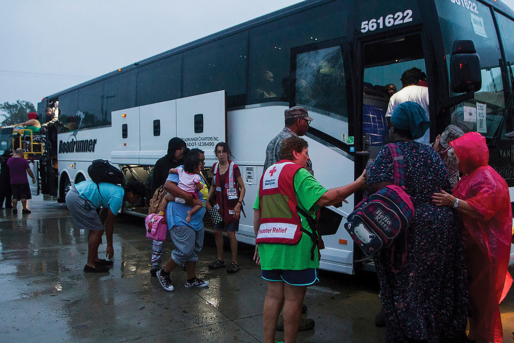 . In this Aug. 27, 2017 photo, Victoria residents are loaded onto buses to be transported from the emergency shelter dome at St. Joseph High School in Victoria, Texas to Austin. The residents are being moved due to rising waters and the city\'s water being shut off. (Nicolas Galindo/The Victoria Advocate via AP)